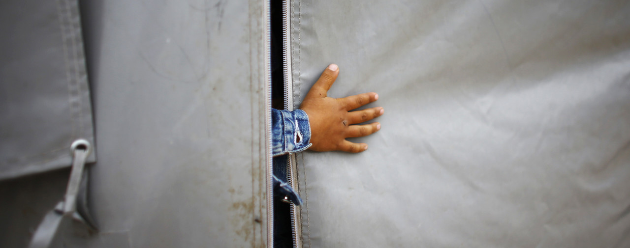 A Kurdish refugee boy from the Syrian town of Kobani sticks his hand out of a tent in a refugee camp in the border town of Suruc, Sanliurfa province November 21, 2014. REUTERS/Osman Orsal (TURKEY - Tags: CIVIL UNREST CONFLICT SOCIETY IMMIGRATION) - RTR4F285